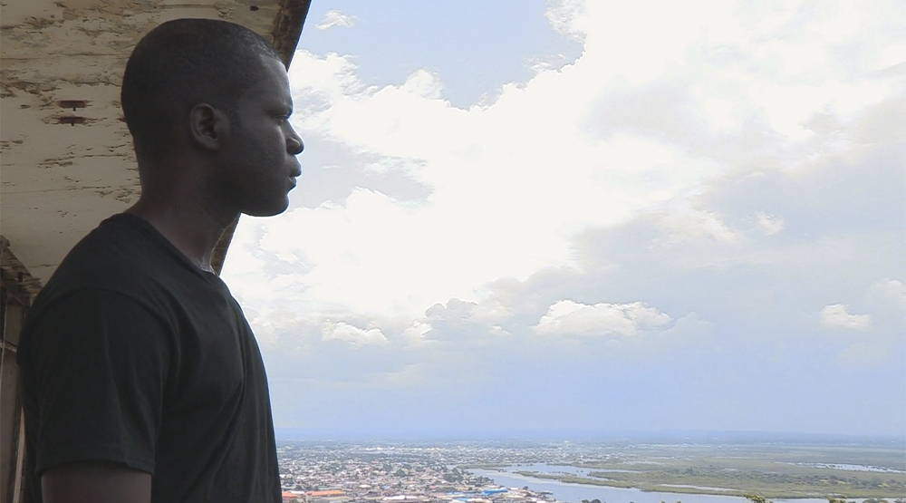 Emmanuel Urey standing over the ruins of the once-grand Ducor Hotel and looking over the slum community of West Point in Monrovia, Liberia. Photo by Sarita Siegel.