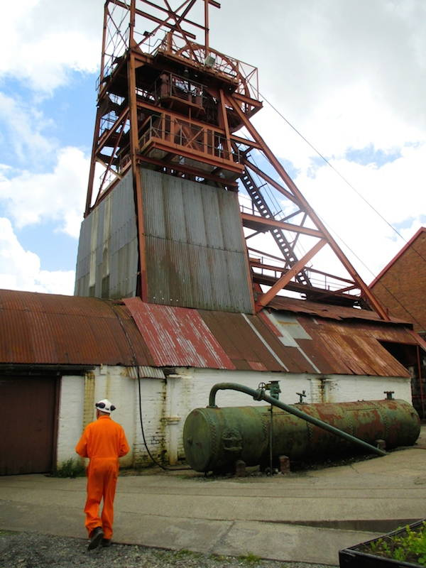 Our tour guide, a retired miner, walking past the headframe at The Big Pit in Blaenavon, Wales. Click to enlarge. (Davey, 2014)