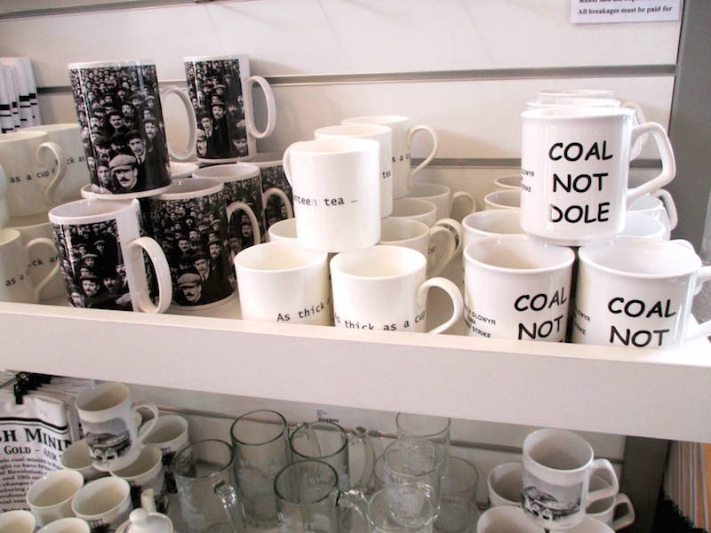 "Mugs from the gift shop at The Big Pit Museum recall the bitter miners strike of 1984-1985. They are emblazoned with ""Coal Not Dole,"" the slogan of the National Union of Mineworkers. ""Dole"" is British slang for unemployment benefits. For some, the mugs might simply be nostalgic kitsch but for others in southern Wales, they represent persistent pride in mining as an occupation. Click to enlarge. (Davey, 2014)"