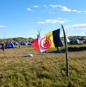 The American Indian Movement flag is a common sight at the camps. Thick vertical bars of red, white, yellow, and black background a red face that is also a raised fist and a peace sign. It can be seen atop flag poles, off the back of pickup trucks, or at individual camps as seen here. Image by author, September 2016.