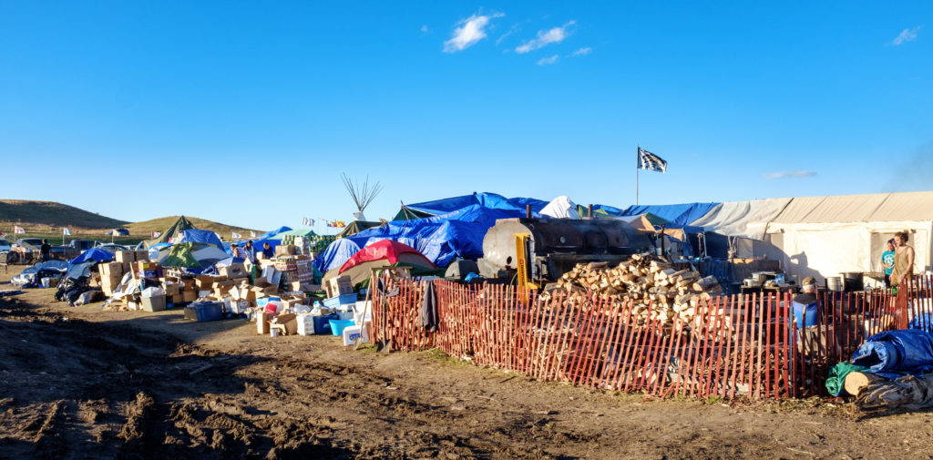 Donations are piled up alongside kitchen and supply tents at the Oceti Sakowin camp. A significant amount of labor at the camps goes into sorting and distributing the supplies that arrive from across the country. Image by author, September 2016.