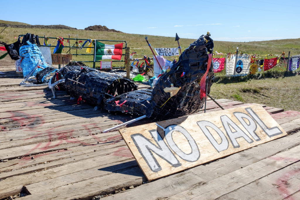"Activists at the Red Warrior Camp produced this sculpture, titled ""Black Snake Killa,"" which evokes a Lakota story of an apocalyptic black snake. The snake has been placed here, at one of the active construction sites, along with banners and signs declaring solidarity from tribes, communities, and social movements from around the world. Image by author, September 2016."