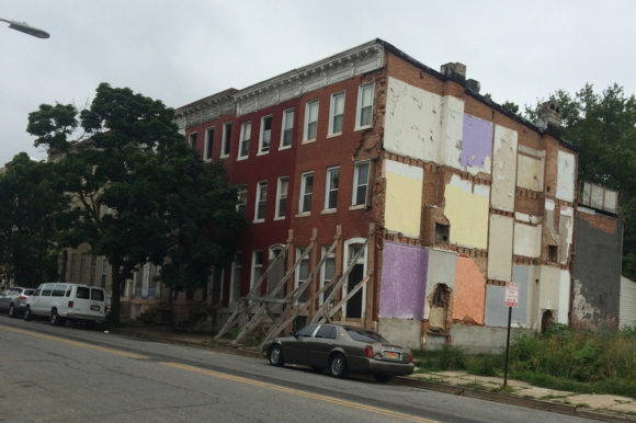 An abandoned building, beginning to fall down, next to an overgrown vacant lot in Baltimore. Photo by Dawn Biehler, 2016.