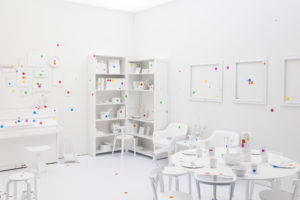 In Obliteration Room, Yayoi Kusama invites her audience at the Helsinki Arm Museum to cover a room with brightly colored dots. Image from Wikimedia Commons, 2017.