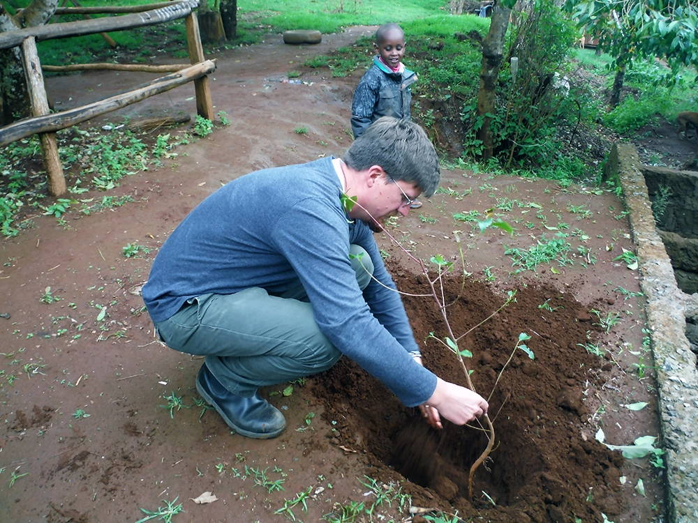 The author planting a maria tree on a smallholder farm. Photo by Isaac Mwenda Mauta, 2014.