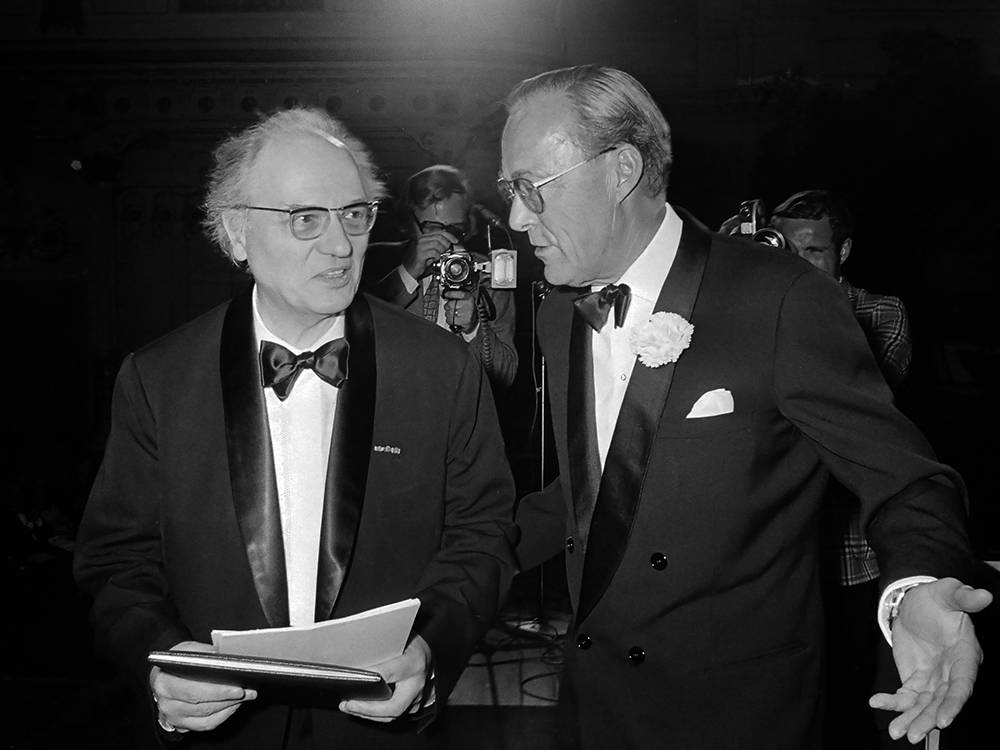 Messiaen holds a sheaf of papers and Prince Bernhard takes his arm and gestures for him to walk forward. Both men wear tuxedos and a film camera and crew capture the scene from behind.