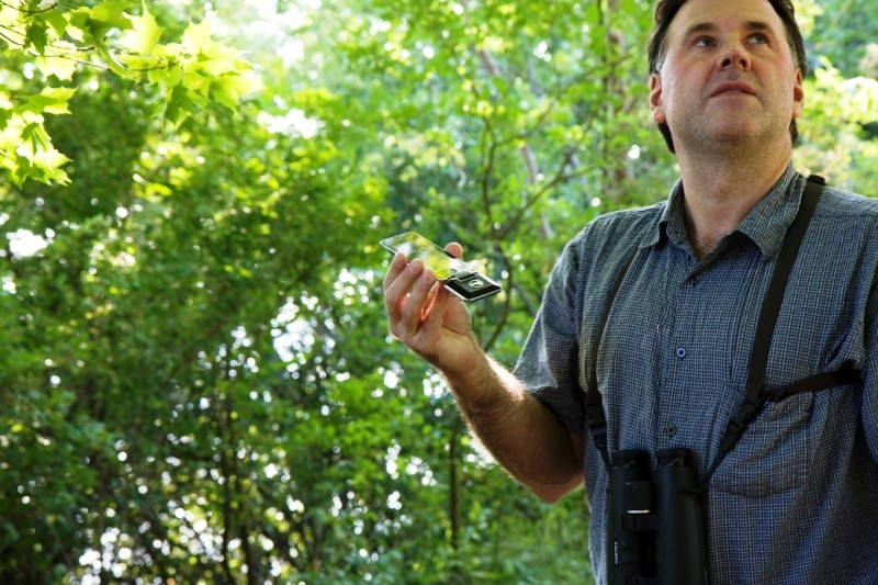 Mark Berres, with binoculars around his neck, stands in the forest looking up at the canopy while holding a smartphone affixed with a thin, black attachment plugged into the bottom.