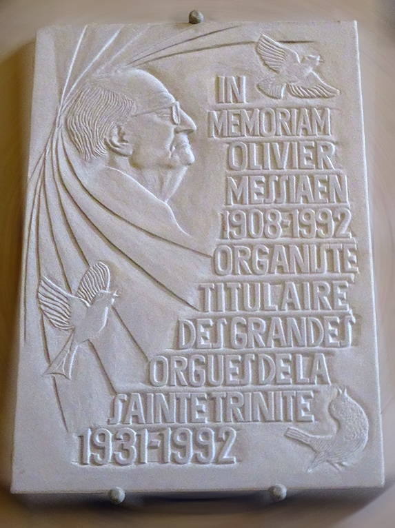 "A white shallow-relief marble plaque, with Messiaen carved in profile, two doves, and a French inscription that reads ""In Memory, Olivier Messiaen, 1908-1992, Organist of the organ of Sainte Trinite, 1931-1992"""