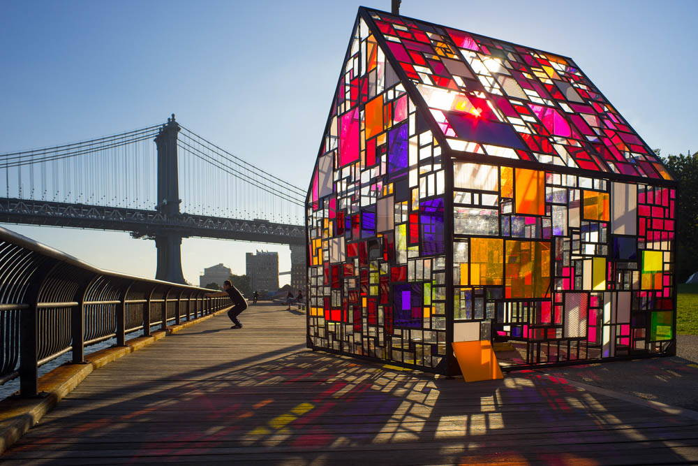 A small house with a multi-colored stained glass exterior. The Brooklyn Bridge in the background.