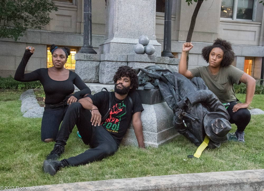 Three young people gather around a bronze statue, lying on its side, and raise their fists.