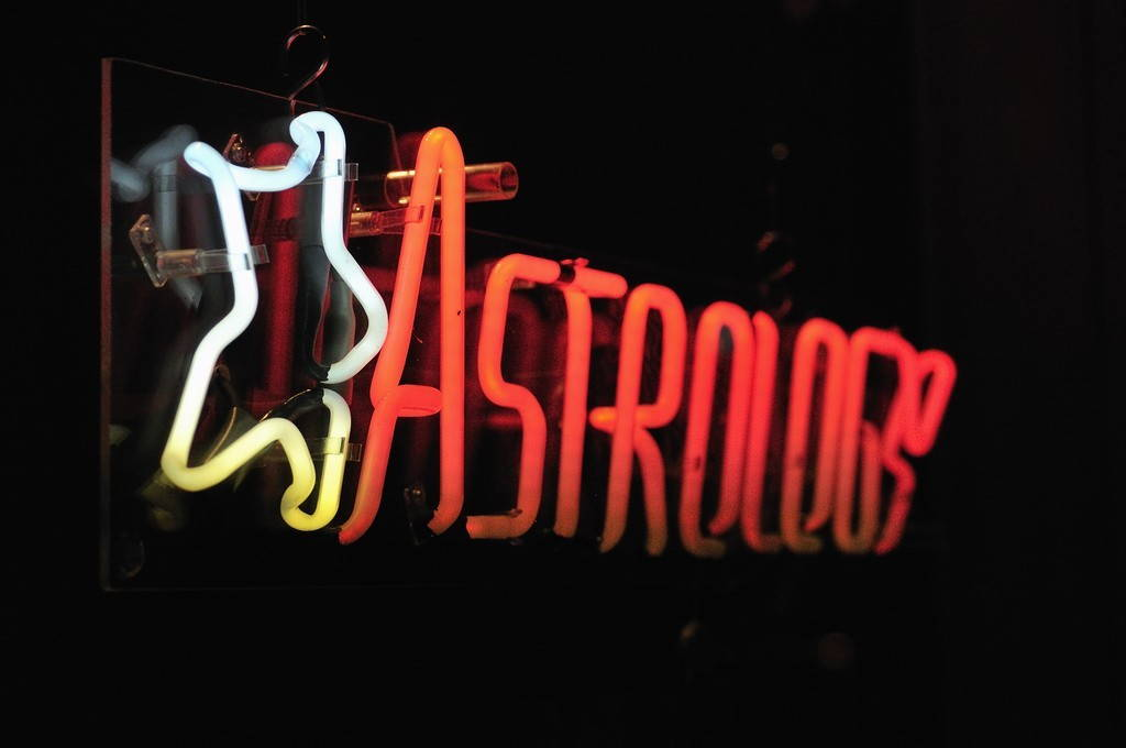"""Astrology"" written in neon with a white neon star, on a black background."