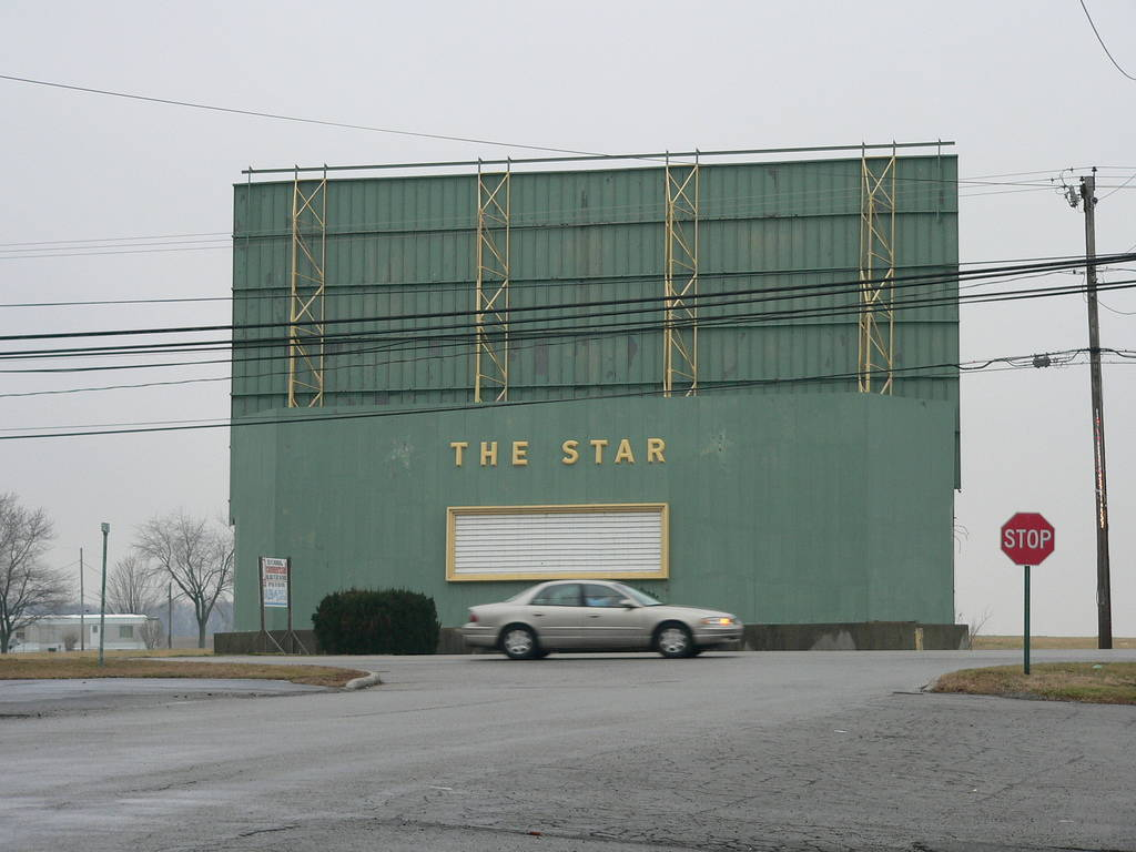 "A blurry car drives past the backside of the abandoned drive-in movie theater, ""The Star."""