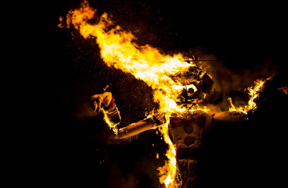 Zozobra, a 50-foot effigy, with its arms raised burns against a black background.