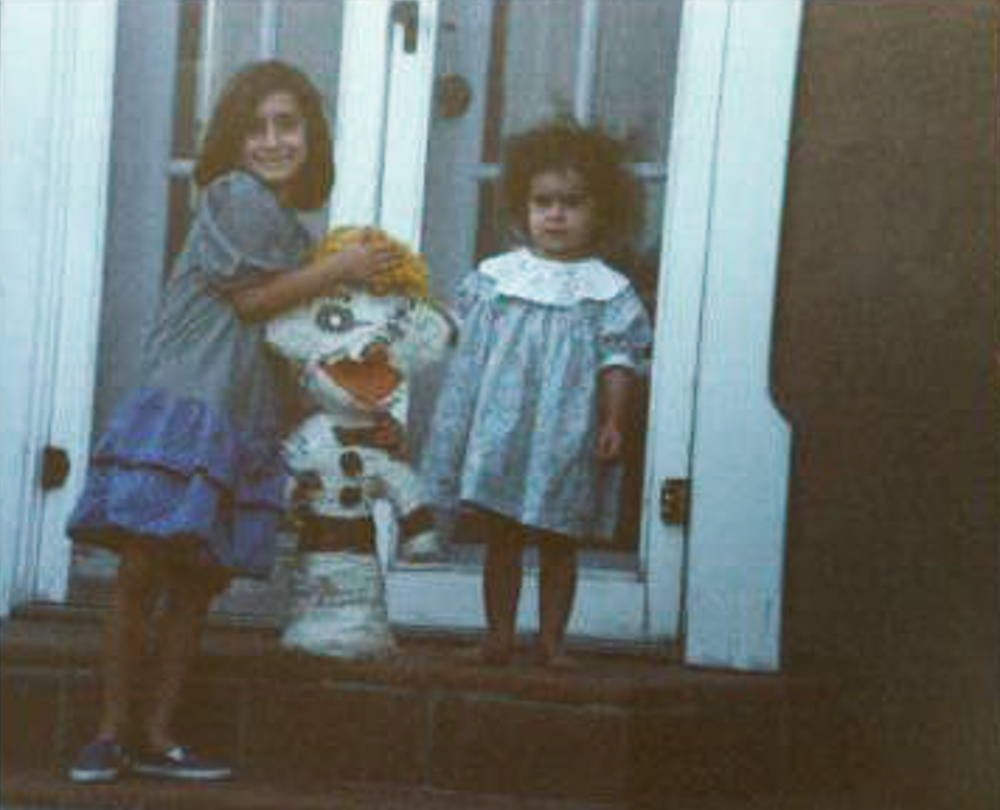 Two young girls in blue dresses stand outside a house holding up a large white Zozobra pinata.