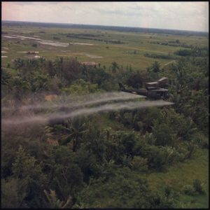 Helicopter sprays defoliation agent on forest during the U.S. war in Vietnam.