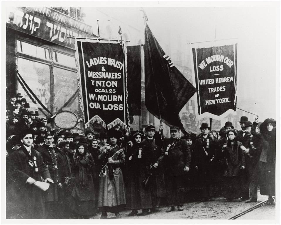 "A black and white photo of a crowd of fair-skinned, dark-haired people in winter clothing hold heavy fabric banners reading ""we mourn our loss"" and the names of two unions--the ""Ladies Waist & Dressmakers Union Local 25"" and ""United Hebrew Trades of New York"". Behind them are storefronts, printed with Hebrew and English words."