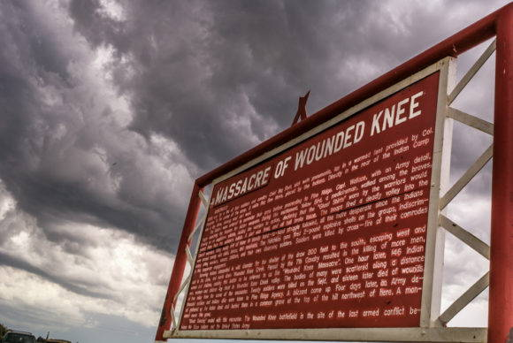 "A large red metal sign, shot from below against a cloudy sky. The title reads ""Massacre of Wounded Knee,"" with the word ""Massacre"" carved onto a panel added to the top of the sign."