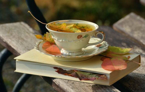 Autumn leaves float upon a tea and saucer resting upon a book.