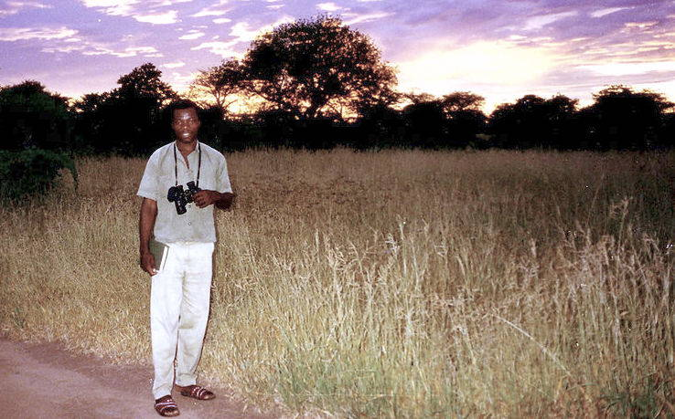 A Tanzanian guide at leading a dawn birdwatching trip. Image from wikimedia commons.