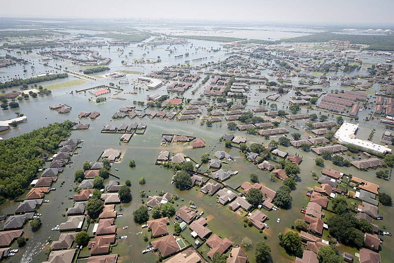 An aerial photograph shows houses flooded up to the roof in Port Arthur, Texas