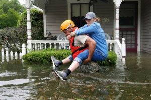 A Texas National Guardsman carries a woman from her flooded home in Houston, TX.