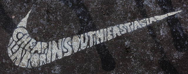 """Street art reads: """"Cheap Labor in Southeast Asia"""" in the shape of the Nike swoosh."""