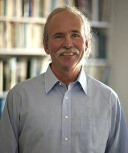 Portrait of Richard White. He is standing in front of a bookshelf and is wearing a light-blue shirt.