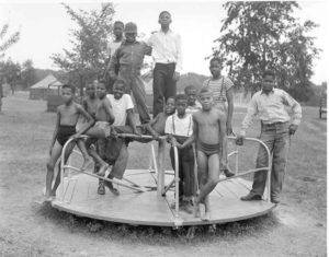 Thirteen African American boys pose for a photograph standing on a playground merry-go-round.