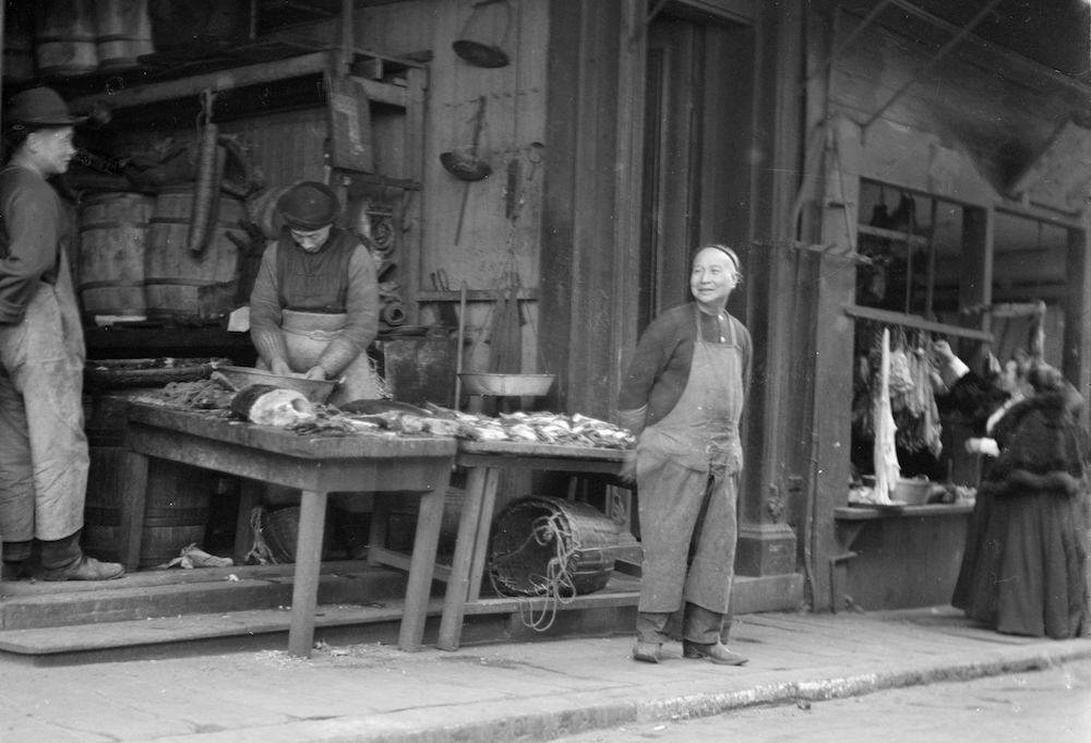 A fishmonger waits for customers at the Chinatown Fish Market in San Francisco co. 1900. Image from Flickr.