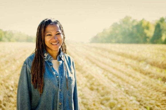 Savi Horne poses, smiling at the camera, in front of a large tilled field against a bright white sky.