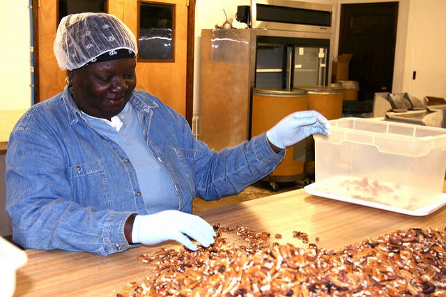 A smiling woman in a hairnet sorts through candied pecans spread out on the table in front of her.