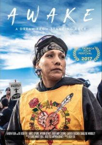 "The movie poster from ""Awake: A Dream from Standing Rock"" depicting a Native woman in a sweatshirt and with ski goggles on her head, looking off to the right with protesters and a bright blue sky in the background."