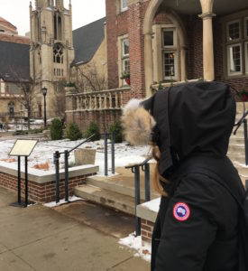 A student wearing a Canada Goose jacket walking across UW-Madison's Library Mall.