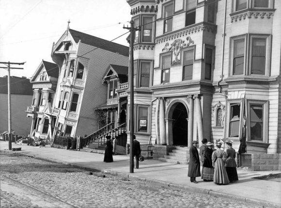 "A group of people stand in front of houses that pitch and lean into one another on the ""Drunken Row"" of Victorian homes at Howard Street (now Van Ness) between 17th and 18th."