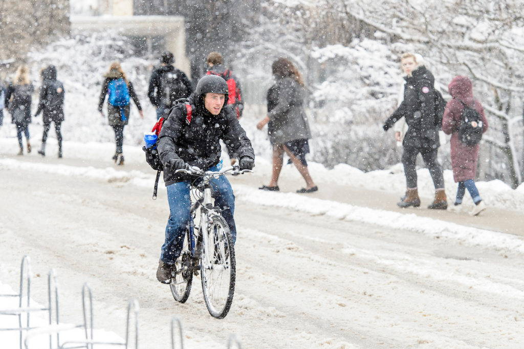 Students on their way to class in snow. One student rides a bike.
