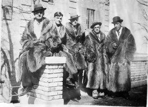 Five college students pose in raccoon fur coats in front of a fraternity house at the University of Wisconsin, Madison.
