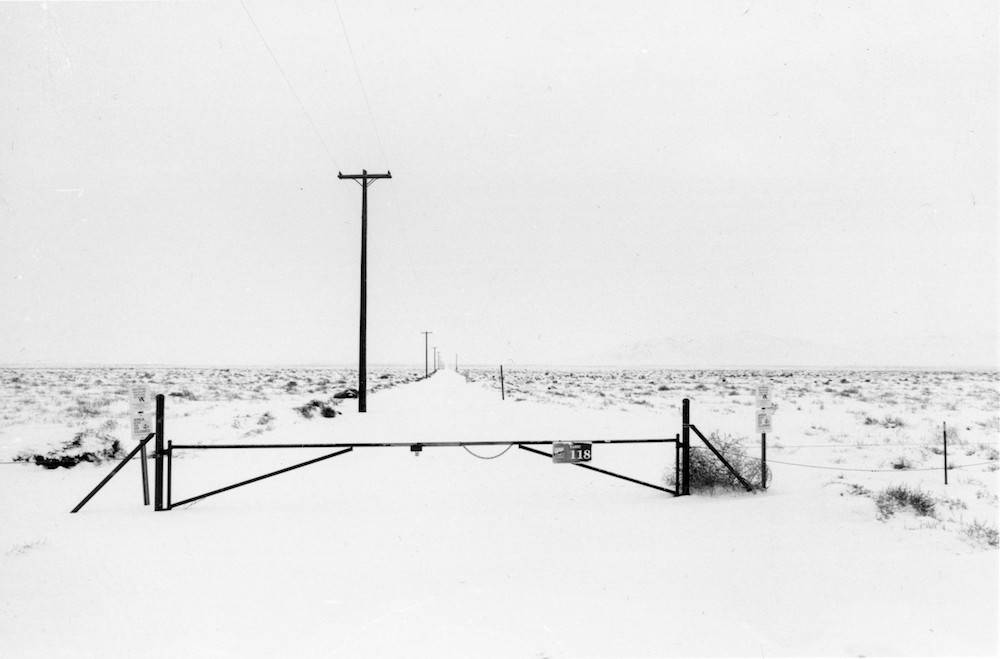In the center of this photograph is a black metal gate and utility pole. The snow covered ground and grey sky make it difficult to see into the distant horizon.