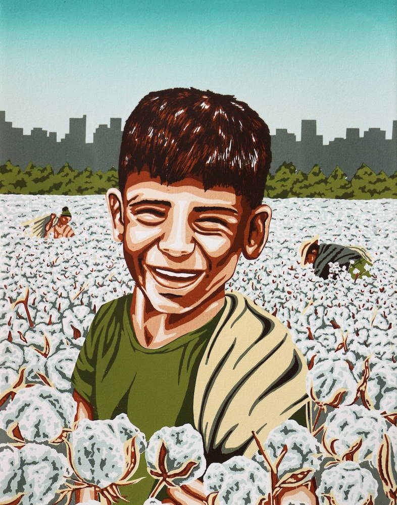 A young boy smiles in a field of cotton; cotton harvesters stoop in the background.