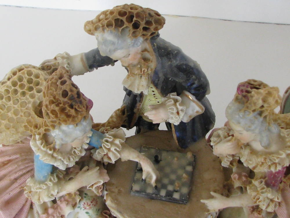 Three women sit at a table playing chess. They are sculpted out of beeswax.